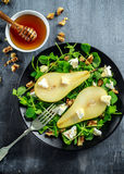 Fresh sweet Pears salad with walnuts, honey and white soft cheese on black plate Royalty Free Stock Images
