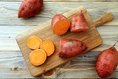 Fresh sweet potatoes on kitchen table background. Top view raw sweet potatoes on kitchen table background royalty free stock photo