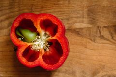 Fresh sweet red pepper cut in half with a growth inside on old wooden background stock photos