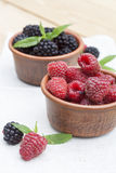 Fresh sweet red raspberry and blueberries in a clay pot and mint on light wooden table. Selective focus Stock Photo