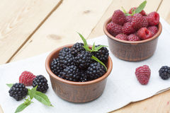 Fresh sweet red raspberry and blueberries in a clay pot and mint on light wooden table. Selective focus Royalty Free Stock Image