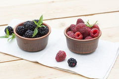 Fresh sweet red raspberry and blueberries in a clay pot and mint on light wooden table. Selective focus Royalty Free Stock Photos