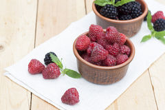 Fresh sweet red raspberry and blueberries in a clay pot and mint on light wooden table. Selective focus Royalty Free Stock Images