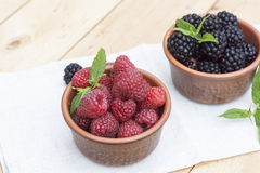 Fresh sweet red raspberry and blueberries in a clay pot and mint on light wooden table. Selective focus Stock Image