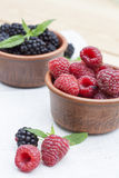 Fresh sweet red raspberry and blueberries in a clay pot and mint on light wooden table. Selective focus Stock Images