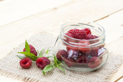Fresh sweet red raspberry in a glass jar and mint on light wooden table. Selective focus Royalty Free Stock Image