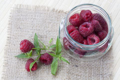 Fresh sweet red raspberry in a glass jar and mint on light wooden table. Selective focus Royalty Free Stock Photos