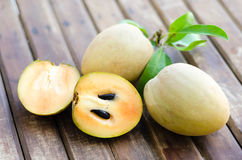 Fresh sweet sapodilla fruit with leaves on wooden background Royalty Free Stock Photo