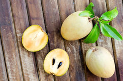 Fresh sweet sapodilla fruit with leaves on wooden background Royalty Free Stock Images