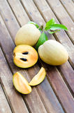 Fresh sweet sapodilla fruit with leaves on wooden background Stock Photo