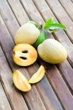Fresh sweet sapodilla fruit with leaves on wooden background Stock Photo