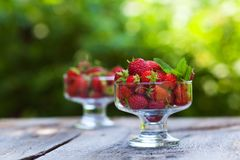 Fresh sweet strawberry in a transparent glass. On a natural background Stock Photos