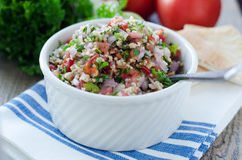 Fresh tabouleh salad. Fresh bulgur tabouleh salad in white bowl and ingredients stock photo