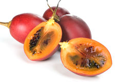Fresh Tamarillos. Whole and halved fresh Tamarillo fruit showing its deep red seeds and tangy sweet flesh Stock Photo