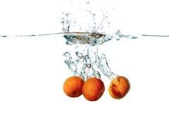 Fresh tangerine fruits falling in water splash Royalty Free Stock Images