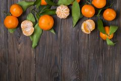 Fresh tangerine oranges on a wooden table. Peeled mandarin. Halves, slices and whole clementines closeup. Bunch of fresh mandarin oranges, whole, halved & Stock Photos