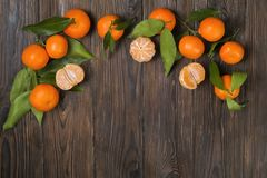Fresh tangerine oranges on a wooden table. Peeled mandarin. Halves, slices and whole clementines closeup. Bunch of fresh mandarin oranges, whole, halved & Stock Images
