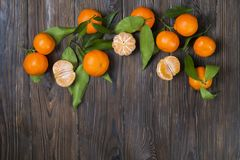 Fresh tangerine oranges on a wooden table. Peeled mandarin. Halves, slices and whole clementines closeup. Bunch of fresh mandarin oranges, whole, halved & Stock Photography