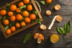 Fresh tangerine oranges on a wooden table. Peeled mandarin. Halves, slices and whole clementines closeup. Fresh mandarin oranges in wooden tray, whole, halved Stock Photography