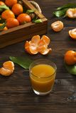 Fresh tangerine oranges on a wooden table. Peeled mandarin. Halves, slices and whole clementines closeup. Fresh mandarin oranges in wooden tray, whole, halved Royalty Free Stock Photography