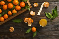 Fresh tangerine oranges on a wooden table. Peeled mandarin. Halves, slices and whole clementines closeup. Fresh mandarin oranges in wooden tray, whole, halved Royalty Free Stock Images