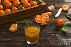 Fresh tangerine oranges on a wooden table. Peeled mandarin. Halves, slices and whole clementines closeup. Fresh mandarin oranges in wooden tray, whole, halved Royalty Free Stock Photo