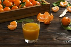 Fresh tangerine oranges on a wooden table. Peeled mandarin. Halves, slices and whole clementines closeup. Fresh mandarin oranges in wooden tray, whole, halved Stock Images