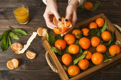 Fresh tangerine oranges on a wooden table. Peeled mandarin. Halves, slices and whole clementines closeup. Fresh mandarin oranges in wooden tray, whole, halved Stock Photo