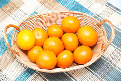 Fresh tangerines in a basket. Some tangerines in a basket on a wooden table Royalty Free Stock Photography