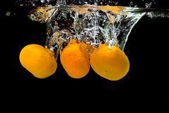 Fresh tangerines dropped into water Royalty Free Stock Photo