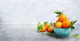 Fresh Tangerines with green leaves in blue bowl over rustic background, side view Royalty Free Stock Image