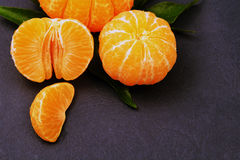 Fresh tangerines with leaves on dark background. Ripe tasty mandarines with green leaves on dark background Stock Photo