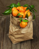 Fresh tangerines with leaves in recycle paper bag on wooden tabl Royalty Free Stock Photos