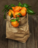 Fresh tangerines with leaves in recycle paper bag on wooden tabl Stock Photos