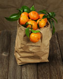 Fresh tangerines with leaves in recycle paper bag on wooden tabl Royalty Free Stock Photography