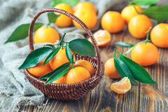 Fresh tangerines with leaves in wicker basket on wooden background, selective focus. Top view. close-up, horizontal Stock Image