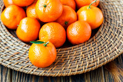 Fresh tangerines with leaves on wicker plate over old wooden table. Close-up, horizontal Stock Photos