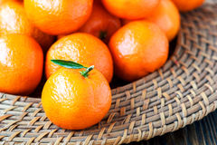 Fresh tangerines with leaves on wicker plate over old wooden table. Close-up, horizontal Royalty Free Stock Photography