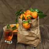 Fresh tangerines in recycle paper bag and glass of juice on wood Royalty Free Stock Images