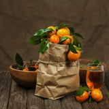 Fresh tangerines in recycle paper bag and glass of juice on wood Stock Photography