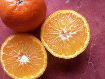 Fresh tangerines on a red table . Slices of a tangerine on a red table royalty free stock photography