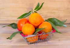 Fresh tangerines and a shopping cart Royalty Free Stock Photos