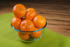 Fresh tangerines in transparent plate on a green tablecloth, wooden table Stock Photo