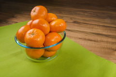 Fresh tangerines in transparent plate on a green tablecloth, wooden table Stock Photos