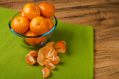 Fresh tangerines in transparent plate on a green tablecloth, wooden table Royalty Free Stock Images