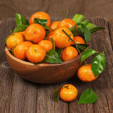 Fresh Tangerines With Leaves In Bowl On Wooden Table. Royalty Free Stock Image