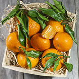 Fresh tangerines in wooden box. Fresh tangerines with leaves in wooden box Royalty Free Stock Photo