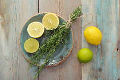 Fresh tarragon. With lemon and lime on wooden background royalty free stock photography