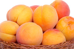 Fresh tasty apricots in a basket. Isolated on white Royalty Free Stock Photos