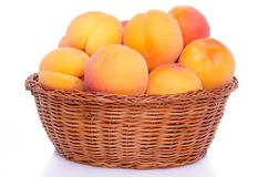 Fresh tasty apricots in a basket. Isolated on white Royalty Free Stock Images
